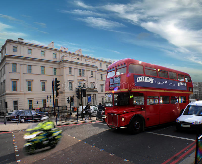 Good morning London, busy street . The busy street of London. Cars, policeman on motorcycle and old red bus (double deck) are lighted by the beautiful royalty free stock photography