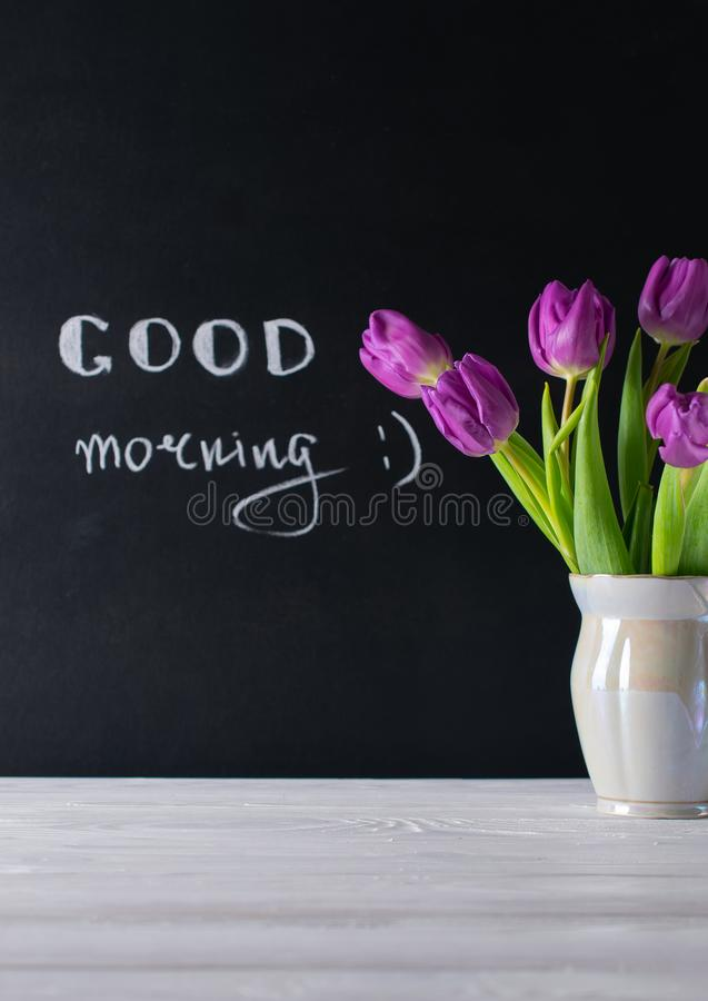 Good morning card, chalk board lettering and beautiful purple tulips bouquet. Good morning composition with purple tulips bouquet on chalk board background royalty free stock photos