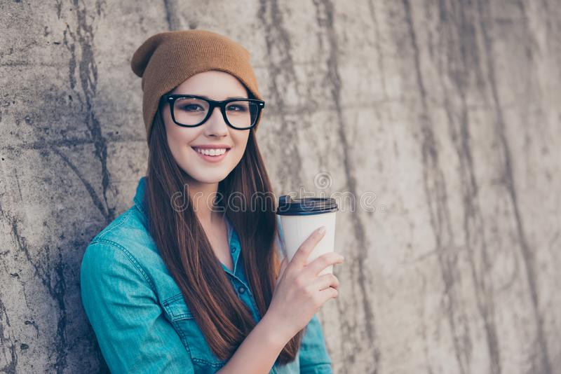 Good morning! Cheerful pretty young lady is having tea near concrete wall outside, smiling, wearing cozy casual royalty free stock photo