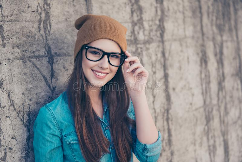 Good morning! Close up of attractive girl, standing near concrete wall outdoors, smiling, fixing her glasses. She is wearing stock photography