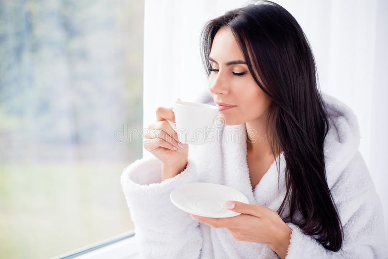 Good morning! Close up portrait of charming dreamy brunette young girl drinking coffee. She is sleepy and relaxed stock photos