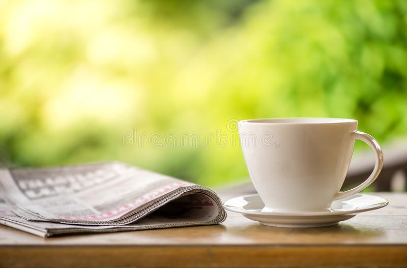 Good morning coffee cup with news paper on nature green background in garden stock images