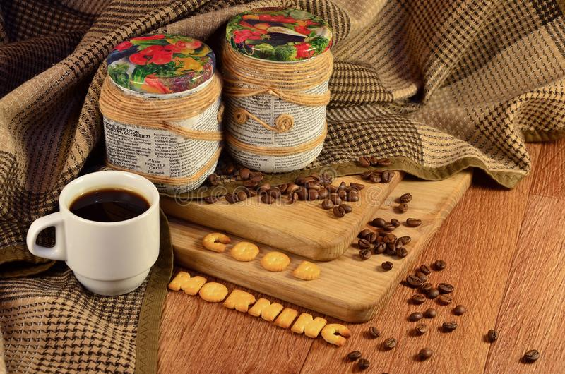 Good morning. Coffee cup and a text, composed of crackers. Still life with coffee cup and two decorative cans with coffee beans, which lie on a wooden surface stock photos