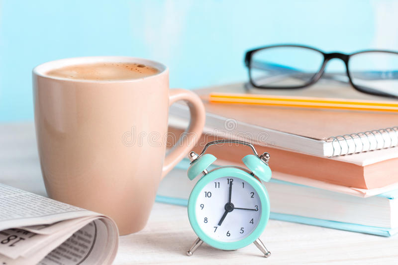 Good morning coffee day start concept. Good morning concept.Mug,alarm clock,newspaper,books,glasses on blue background.morning coffee day start.Education stock photos