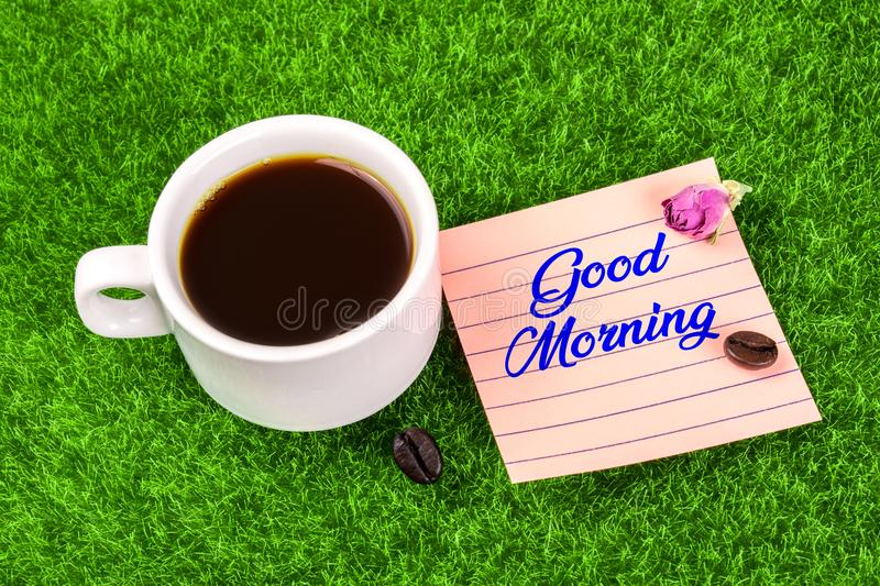 Good morning with coffee. Good morning word in memo with coffee cup , coffee bean and dried rose bud on grass stock photos