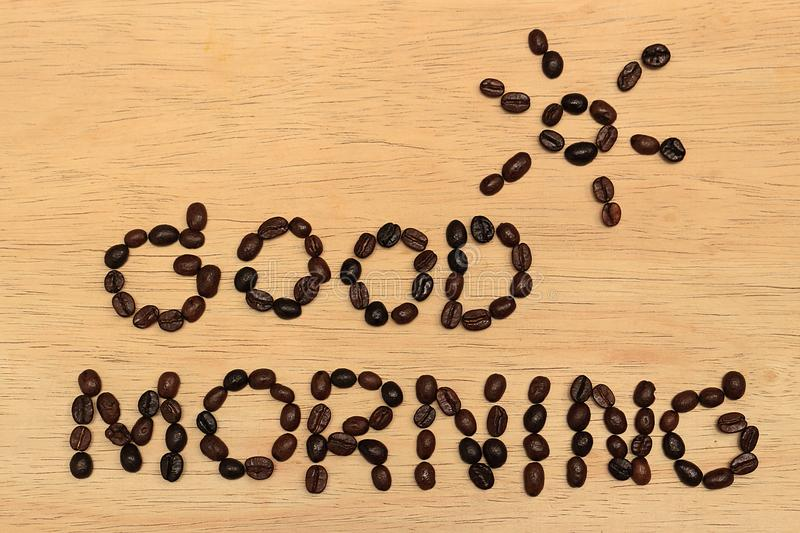 Good Morning Coffee. There is a message `GOOD MORNING` and a picture of the sun above the message, all made of coffee beans, the backdrop is a wooden board royalty free stock image