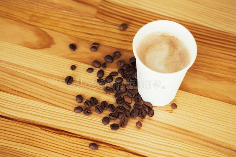 Good Morning. Coffee Time. Coffee to go and beans on a wooden background.  stock photo