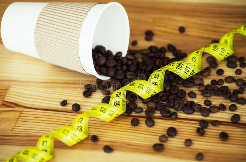 Good Morning. Coffee Time. Coffee to go and beans on a wooden background.  royalty free stock photo