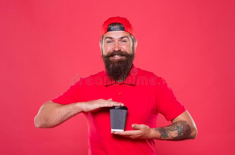 Good morning coffee to go. Positive morning. bearded man drink tea red background. brutal hipster in uniform. happy. Barista hold coffee cup. take away coffee stock photo