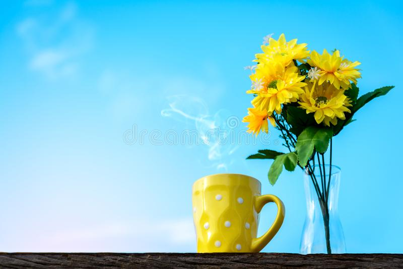 Good morning coffee and yellow flower vase. On a wooden table in the sunrise sky background royalty free stock photo