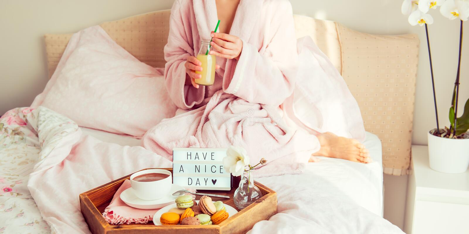 Good morning concept. Breakfast in bed with Have a nice day text on lighted box, coffee and macaroons on tray and blurred woman in stock photo