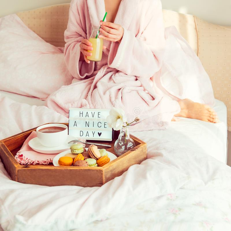 Good morning concept. Breakfast in bed with Have a nice day text on lighted box, coffee and macaroons on tray and woman in. Bathrobe drinking juice. Hospitality royalty free stock photos