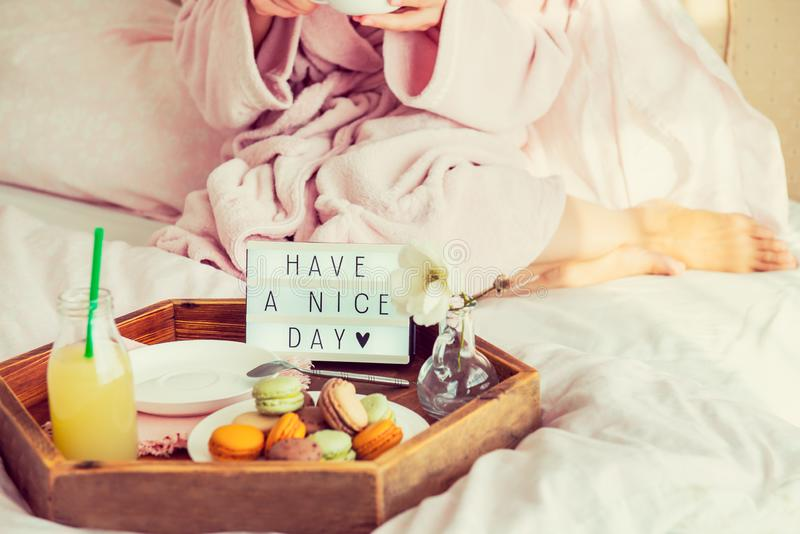 Good morning concept. Breakfast in bed with Have a nice day text on lighted box, juice and macaroons on tray and blurred woman in. Bathrobe drinking coffee royalty free stock photo