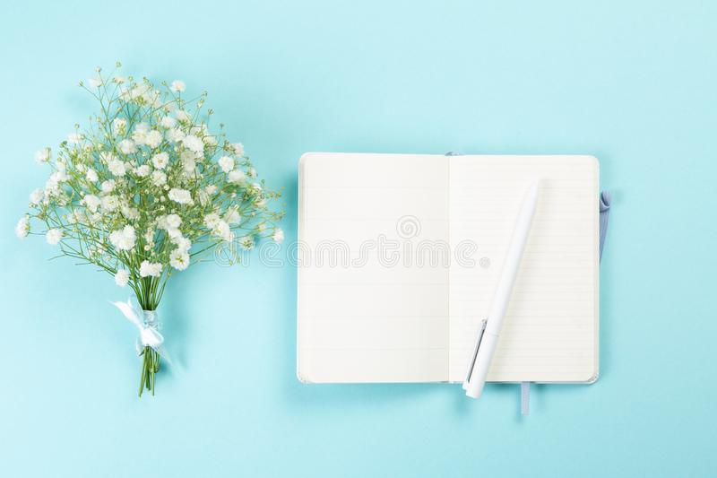 Good morning concept - coffee, flowers, notebook. Blue background top view stock photo