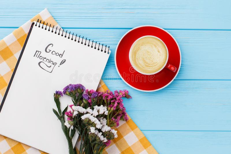 Good morning concept, cop of coffee and flowers. Pleasant surprise for girlfriend. Blue wooden table background royalty free stock image