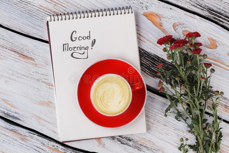 Good morning concept, flat lay. Cup of coffee, red flowers and notepad. White wood background, top view stock images