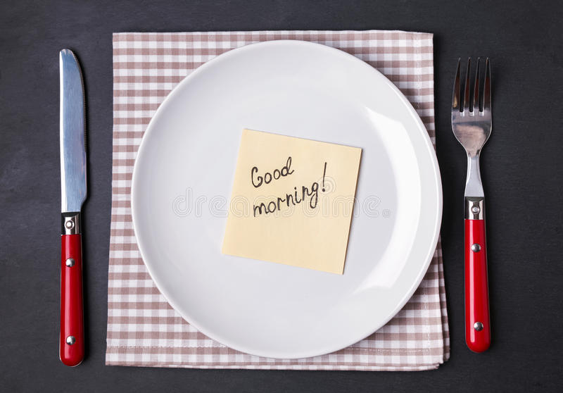 Good morning concept. Fork, knife and empty plate with paper note with text. Good morning concept royalty free stock photo