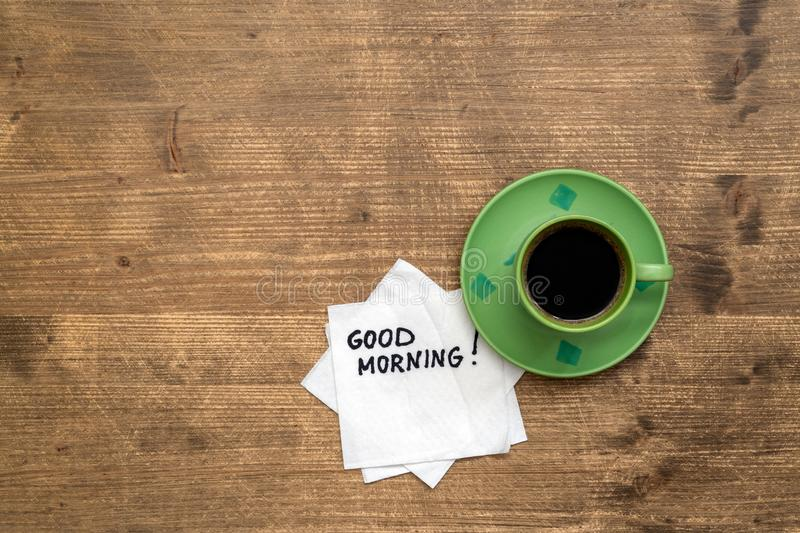 Good morning concept. Motivational slogan on a napkin with a cup of coffee royalty free stock photography