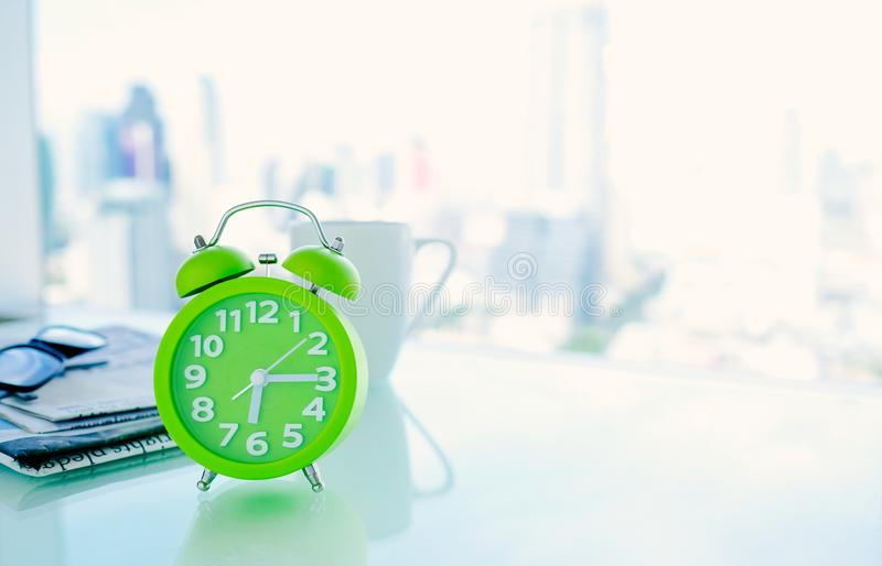 Good morning concept. Alarm clock closeup. Good morning concept. The table clock has a nice day with a cup of coffee and a newspaper flower pot, located near the royalty free stock photos