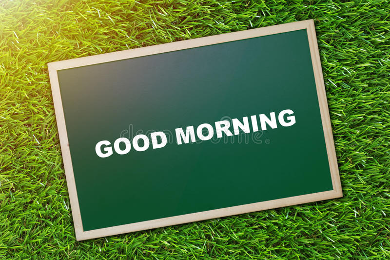 Good Morning Concept. Good morning and wake up concept, greeting text on blackboard, green grass background stock photo