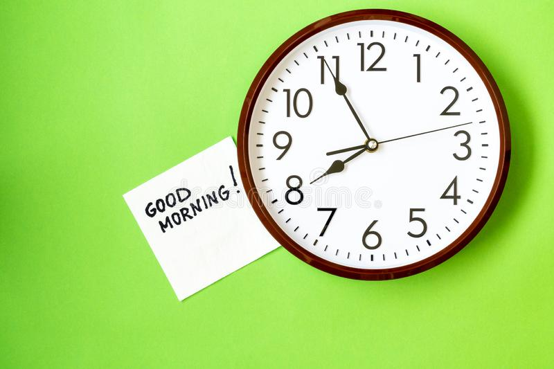 Good morning concept. Wall clock with GOOD MORNING note on napkin royalty free stock photography