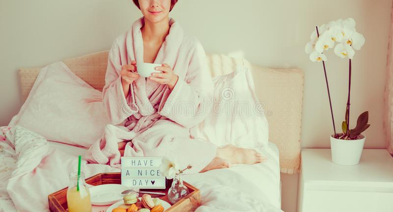 Good morning concept. Woman in bathrobe sitting on the bed, drinking coffee and has her breakfast in bed with Have a nice day text. On lighted box. Hospitality stock images