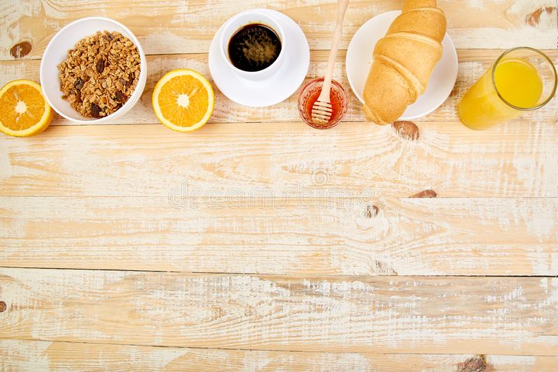 Good morning.Continental breakfast on ristic wooden background. Cup of coffee, orange juice, croissants, granola muesli on wooden. Tray from above. Top view royalty free stock photo