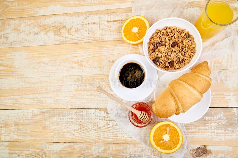 Good morning.Continental breakfast on ristic wooden background. Cup of coffee, orange juice, croissants, granola muesli on wooden. Tray from above. Top view stock images