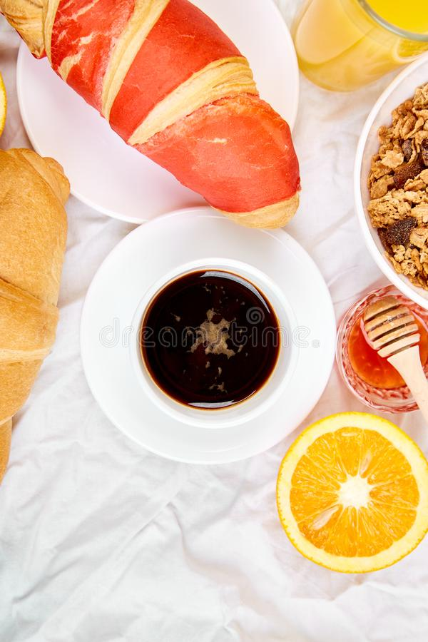 Good morning. Continental breakfast on white bed sheets. Cup of coffee, orange juice, croissants, jam muesli, granola, from above. Top view. Flat lay. Copy stock image