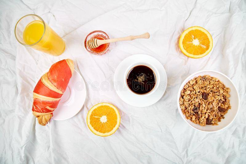 Good morning. Continental breakfast on white bed sheets. Cup of coffee, orange juice, croissants, jam muesli, granola, from above. Top view. Flat lay. Copy stock photo