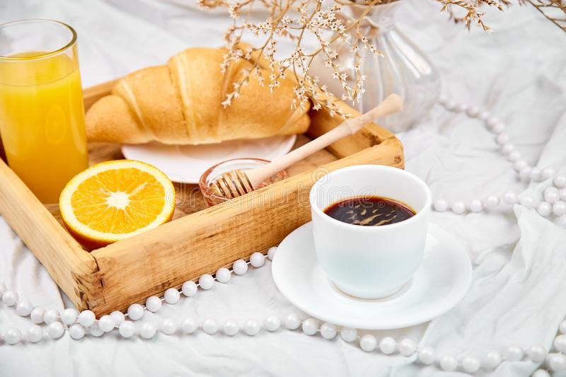 Good morning. Continental breakfast on white bed sheets. Cup of coffee, orange juice, croissants, jam on wooden tray from above. Top view. Flat lay. Copy space stock images