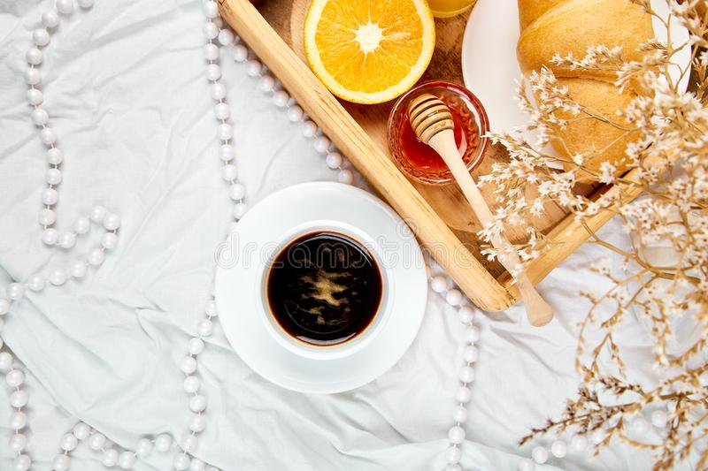 Good morning. Continental breakfast on white bed sheets. Cup of coffee, orange juice, croissants, jam on wooden tray from above. Top view. Flat lay. Copy space royalty free stock photo