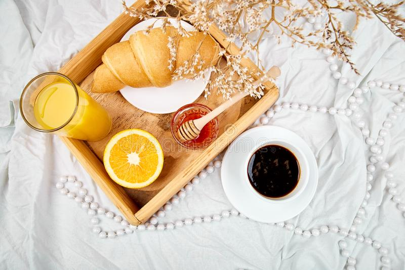 Good morning. Continental breakfast on white bed sheets. Cup of coffee, orange juice, croissants, jam on wooden tray from above. Top view. Flat lay. Copy space stock photography
