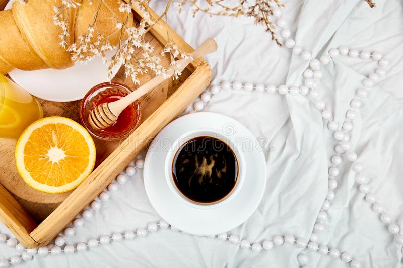 Good morning. Continental breakfast on white bed sheets. Cup of coffee, orange juice, croissants, jam on wooden tray from above. Top view.  Flat lay. Copy stock photography