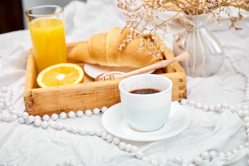 Good morning. Continental breakfast on white bed sheets. Cup of coffee, orange juice, croissants, jam on wooden tray from above. Top view. Flat lay. Copy space stock image