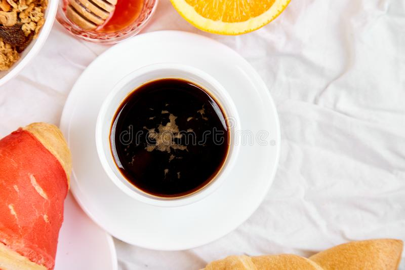 Good morning. Continental breakfast on white bed sheets. Cup of coffee, orange juice, croissants, jam muesli, granola, from above. Top view. Flat lay. Copy stock images