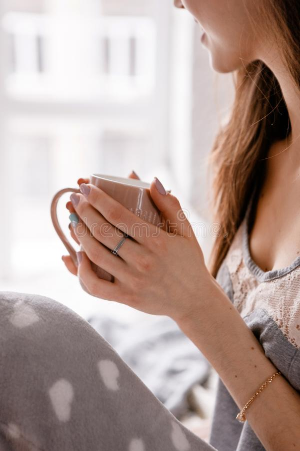 Good morning with cup of coffee. Beautiful unrecognizable young woman in nightwear meets sunrise near window, enjoyment and calmness, sensuality and comfort royalty free stock images