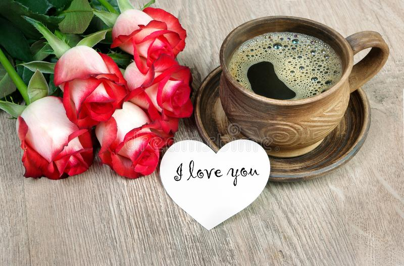 Good morning. a cup of coffee and a red roses on a wooden table. I love you. stock photos