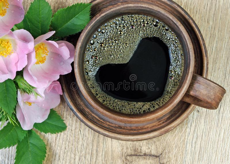 Good morning. a cup of coffee and a red wild rose on a wooden table. heart is a symbol of love. Good morning. a cup of coffee and a red wild rose on a wooden stock photography