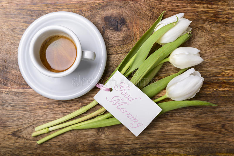 Good morning. Cup of coffee, white tulips and card with good morning written on wooden table top view stock photos