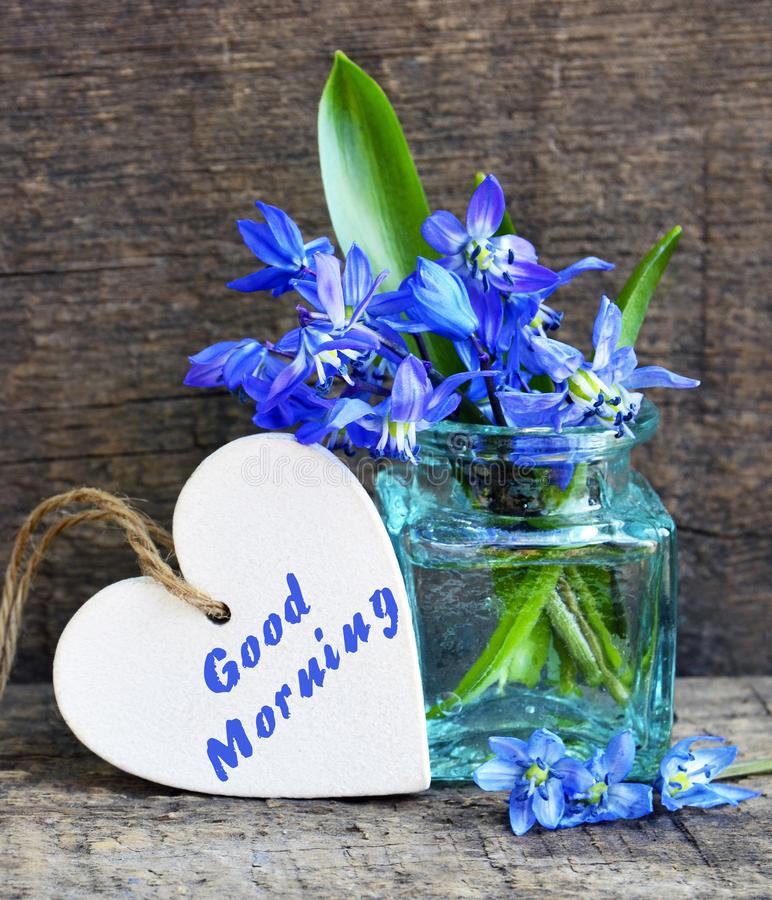 Good Morning.Decorative white wooden heart with text and bouquet of blue scilla spring flowers in a glass vase on old wooden backg. Round.Selective focus stock photo