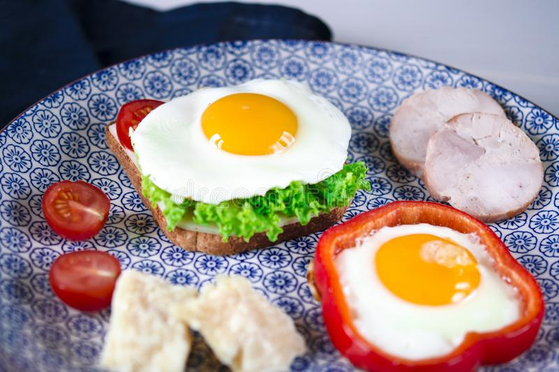 Sandwich with egg, ham, cheese, toast and salad leaves lies on a plate with tomato and dill stock photography