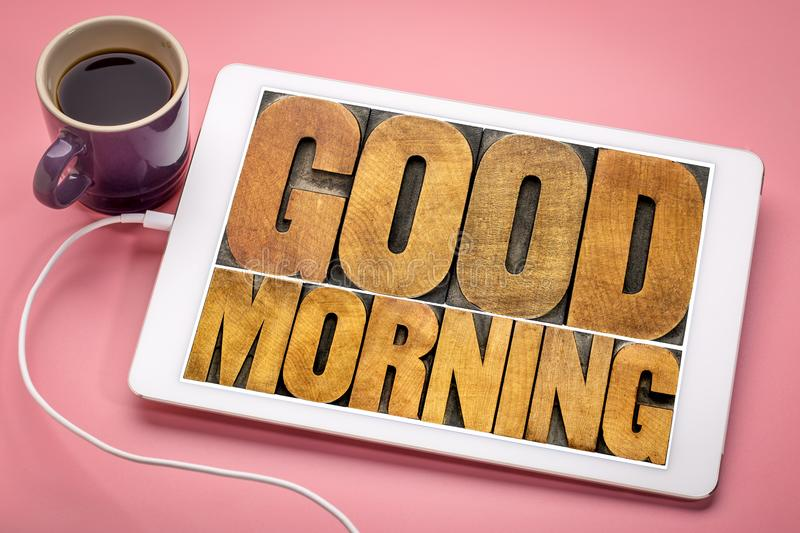 Good Morning on digital tablet. Good Morning word abstract - text in vintage letterpress wood type printing blocks on a digital tablet with a cup of coffee royalty free stock photography