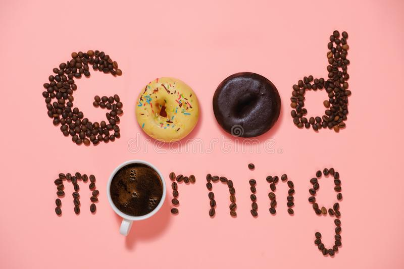 Good morning, donuts and coffee. A cup of good morning coffee with donuts and grains on a pink background top view royalty free stock image