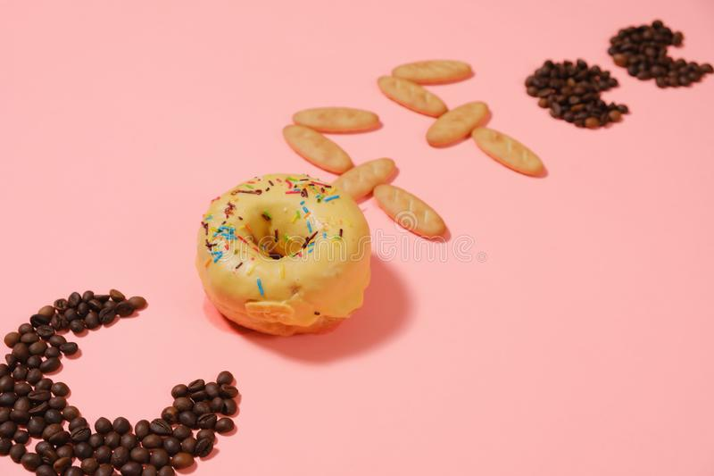 Good morning, donuts and coffee. A cup of good morning coffee with donuts and grains on a pink background top view royalty free stock images