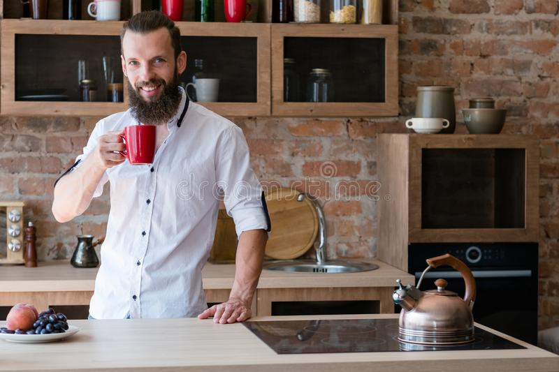 Good morning drink habit man cup kitchen. Good morning. Hot drink energy. Habit and ritual. Young man with cup of beverage looking at camera. Loft kitchen space royalty free stock images