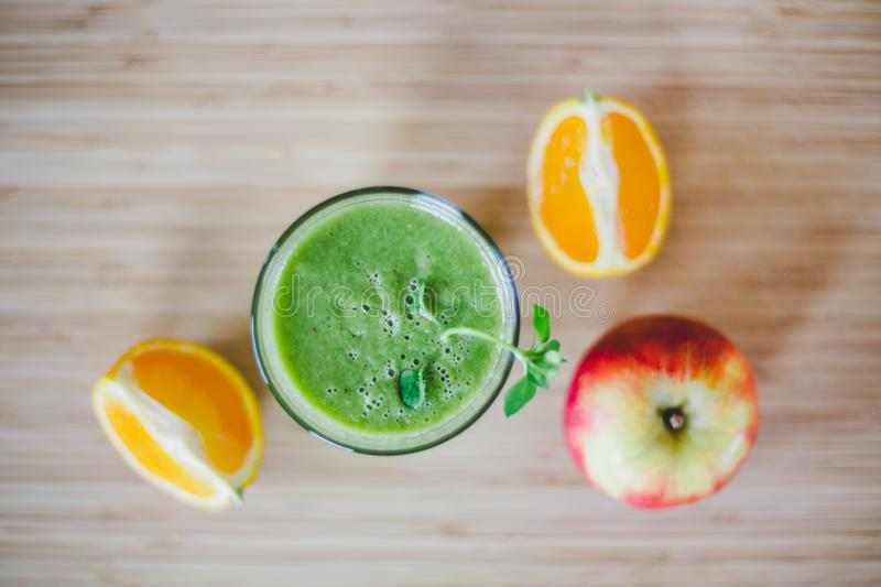 Good morning: Fresh green smoothie and fruits on wooden background, healthy breakfast. Arrangement of a fresh green healthy smoothie and fruits on a wooden royalty free stock image