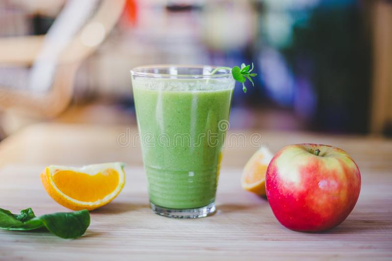 Good morning: Fresh green smoothie and fruits on wooden background, healthy breakfast. Arrangement of a fresh green healthy smoothie and fruits on a wooden royalty free stock photo