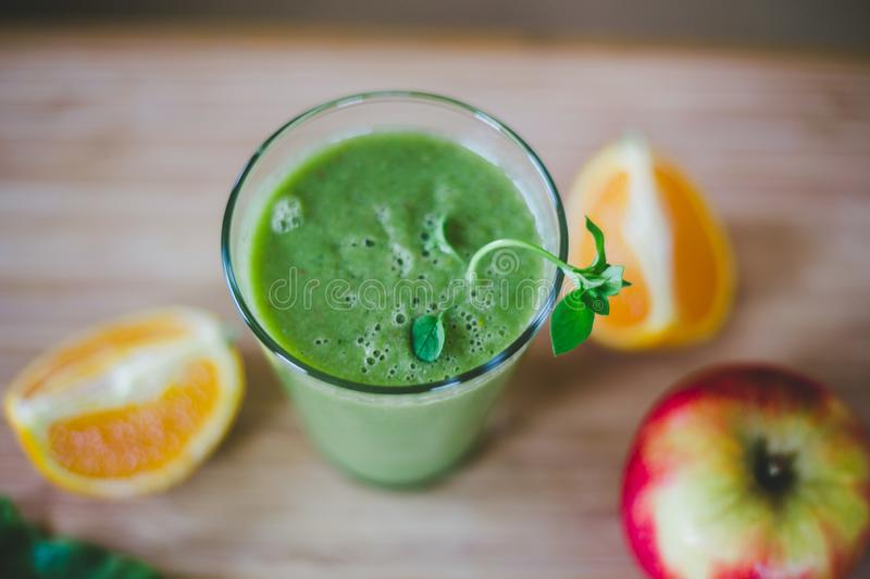 Good morning: Fresh green smoothie and fruits on wooden background, healthy breakfast. Arrangement of a fresh green healthy smoothie and fruits on a wooden stock photography