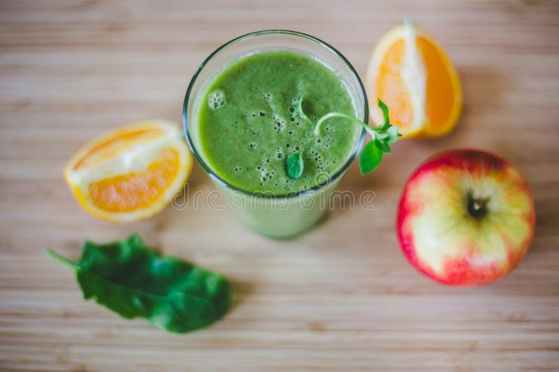 Good morning: Fresh green smoothie and fruits on wooden background, healthy breakfast. Arrangement of a fresh green healthy smoothie and fruits on a wooden stock photos